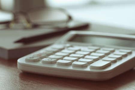 calculadora: Close up de documentos de negocios en la mesa de la oficina con la calculadora y anteojos Foto de archivo