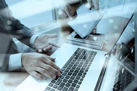 tecnología informatica: Documentos de negocios en la mesa de oficina con teléfono inteligente y la tableta digital y el ordenador portátil y dos colegas datos discutiendo