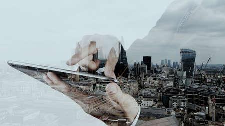 exposici�n: Doble exposici�n de negocios que trabajan con el nuevo equipo moderno y fondo londres ciudad como concepto Foto de archivo