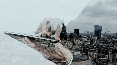 contact info: Double exposure of businessman working with new modern computer and london city background as concept