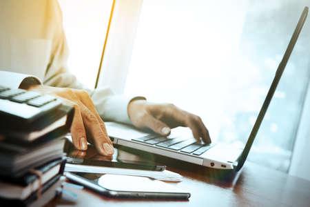 デジタル タブレットとラップトップとノートブックのスタックと目のガラス オフィスの木製の机に取り組んでデザイナーの手 写真素材 - 42124529