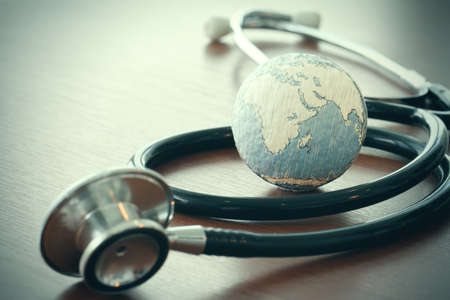 global health: stethoscope and texture globe with digital tablet as medical network concept
