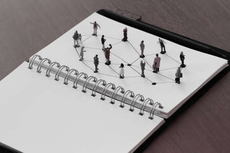 teamwork concept: close up of miniature people with social network diagram on open notebook on wooden desk as social media concept