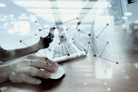 ソーシャル メディア ネットワーク図では木製の机の上のノート パソコンに取り組んでいるビジネス人間手の二重露光