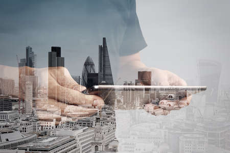 Double exposure of success businessman using digital tablet with london building and social media diagram