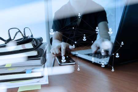 network diagram: double exposure of designer hand working with digital tablet and laptop and notebook stack and eye glass with social network diagram on wooden desk in office
