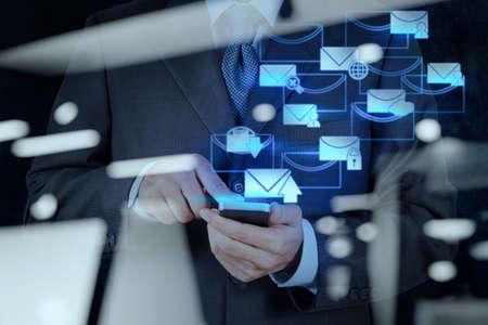 correo electronico: doble exposici�n de la mano de negocios usan la computadora del tel�fono inteligente con el icono de correo electr�nico como concepto