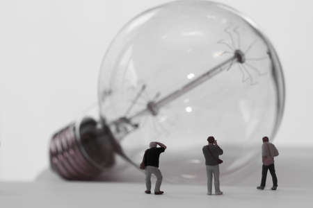 miniature: Creative idea concept - miniature photographer with vintage light bulb on open paper notebook Stock Photo