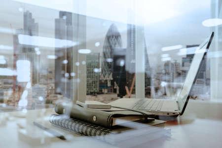 ノート パソコンとスマート フォン木製テーブルとロンドン市内に仕事場がぼやけて背景