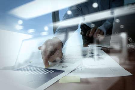 ソーシャル メディア ダイアグラムでラップトップ コンピューターをオフィスのテーブルにビジネス ドキュメントを扱うビジネスマン手の二重露光
