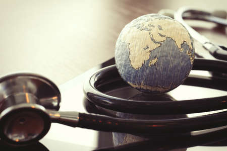 fonendoscopio: stethoscope and texture globe with digital tablet as medical network concept