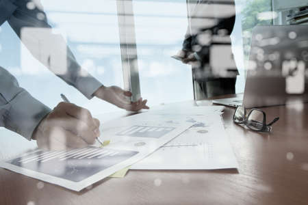 double exposure of business documents on office table with smart phone and digital tablet and stylus and two colleagues discussing data in the background Imagens