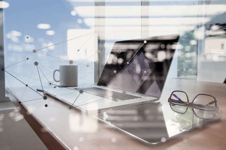 workplaces: Office workplace with laptop and smart phone on wood table with eyeglasses on digital tablet