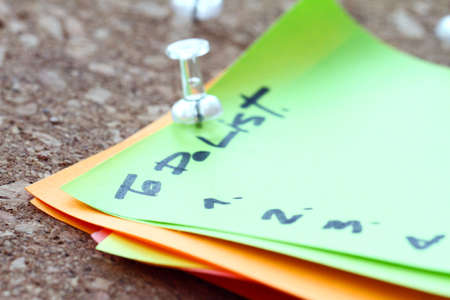 note board: close up of pin and to do list word on sticky note with cork board as concept Stock Photo