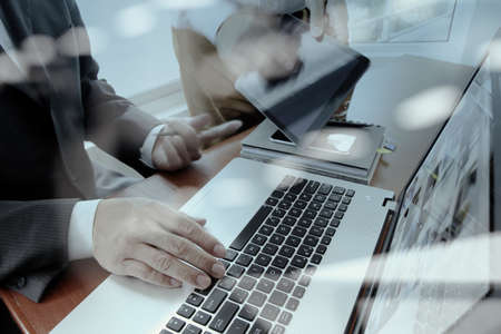 gente trabajando: documentos de negocios en la mesa de oficina con teléfono inteligente y un ordenador portátil y dos colegas en discusiones datos en segundo plano Foto de archivo