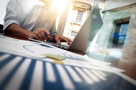 商務: 辦公桌子商務文件與智能手機和平板電腦的數字和圖形業務圖和男子在後台運行
