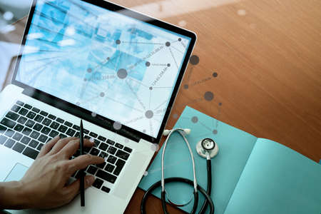 health technology: top view of Medicine doctor hand working with modern computer and smart phone with social media network on wooden desk as medical concept Stock Photo