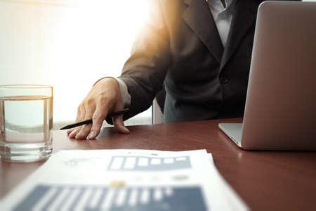 lapiz y papel: documentos de negocios en la mesa de oficina con teléfono inteligente y la tableta digital y diagrama de negocio gráfico y hombre que trabajan en segundo plano