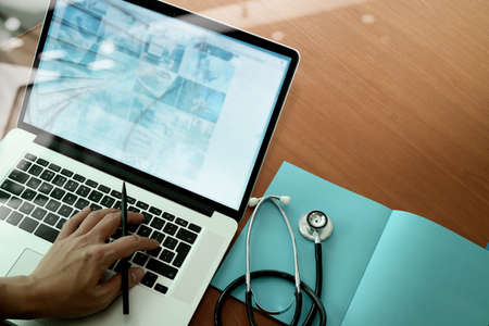 Draufsicht Medizin Arzt der Hand die Arbeit mit modernen Computer-und Smartphone auf Schreibtisch aus Holz, wie medizinische Konzept