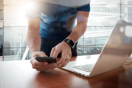 smart: designer hand working and smart phone and laptop on wooden desk in office with london city background Stock Photo