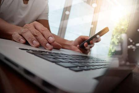 usando computadora: de trabajo de mano del diseñador y el teléfono inteligente y portátil de escritorio de madera en la oficina con el fondo de la ciudad de Londres