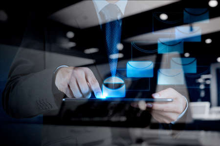 correspond: double exposure of businessman hand use tablet computer with virtual email icon