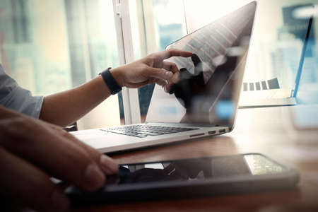 empresario: de trabajo de mano del dise�ador y el tel�fono inteligente y port�til de escritorio de madera en la oficina con el fondo de la ciudad de Londres