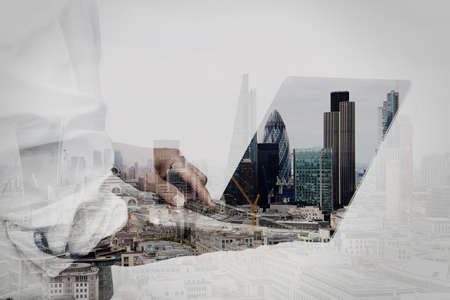 london people: double exposure of businessman working on his laptop in office with london city background