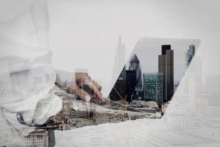 studie: Double Exposure podnikatel pracuje na jeho notebooku v kanceláři s London City pozadím