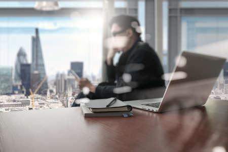 ejecutivo en oficina: de trabajo de mano del diseñador y el teléfono inteligente y portátil de escritorio de madera en la oficina con el fondo de la ciudad de Londres