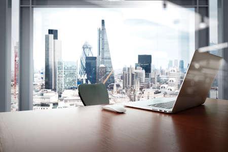 papeles oficina: Lugar de trabajo de oficina con el ordenador port�til y el tel�fono inteligente en mesa de madera con fondo londres ciudad Foto de archivo