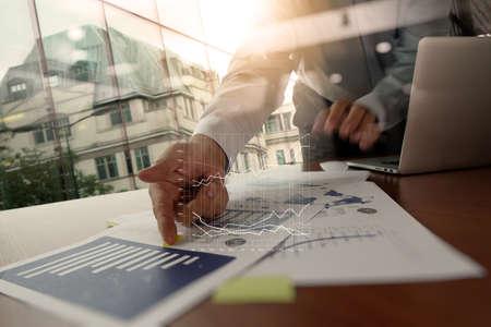 negocio: Doble exposición de hombre de negocios la mano, trabajando en equipo portátil pantalla en blanco en el escritorio de madera como concepto