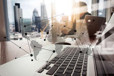 persone: mano progettista di lavoro e di smart phone e computer portatile sulla scrivania in legno in ufficio con sfondo London City con lo schema di social media