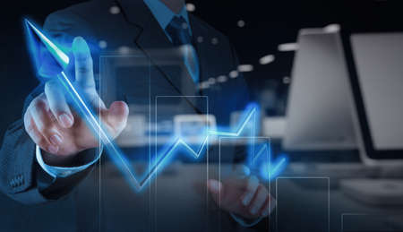 successful investment: double exposure of businessman hand pointing virtual chart business on touch screen computer Stock Photo