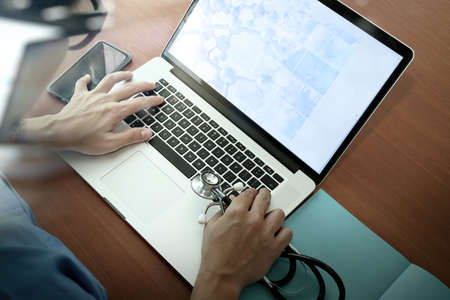 医療概念としての木製机の上現代のコンピューターとスマート フォンの使用医学医師の手の上から見る