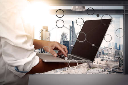 to browse: businessman working on his laptop in office and social network diagram with london city background