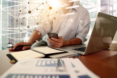 デザイナーの手のスマート フォンとソーシャル メディア ダイアグラムとロンドンの街の背景が付いているオフィスの木製の机の上のノート パソコ 写真素材