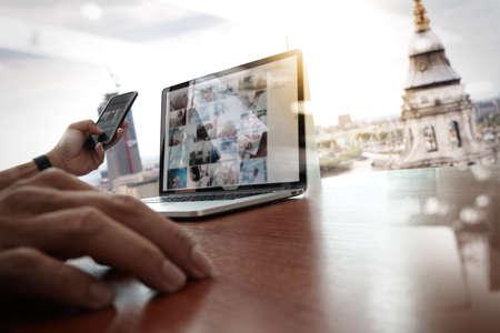 trabajo social: de trabajo de mano del diseñador y el teléfono inteligente y portátil de escritorio de madera en la oficina con el fondo de la ciudad de Londres