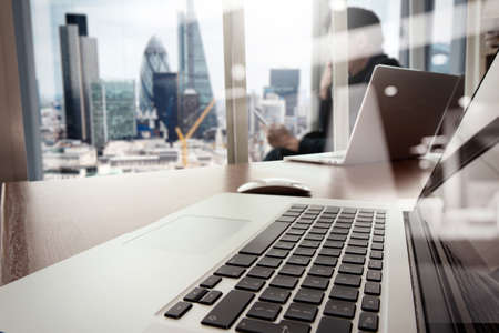 puesto de trabajo: de trabajo de mano del dise�ador y el tel�fono inteligente y port�til de escritorio de madera en la oficina con el fondo de la ciudad de Londres