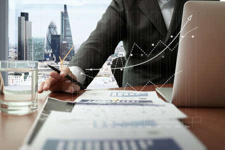 Documents d'affaires sur la table de bureau avec téléphone intelligent et tablette numérique et graphique affaires diagramme et homme travaillant dans l'arrière-plan avec vue london ville Banque d'images - 44715174