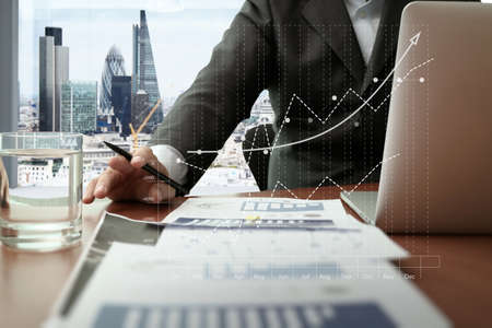 business documents on office table with smart phone and digital tablet and graph business diagram and man working in the background with london city view Standard-Bild