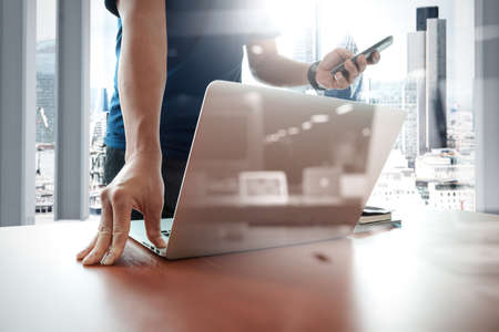 people office: designer hand working and smart phone and laptop on wooden desk in office with london city background Stock Photo
