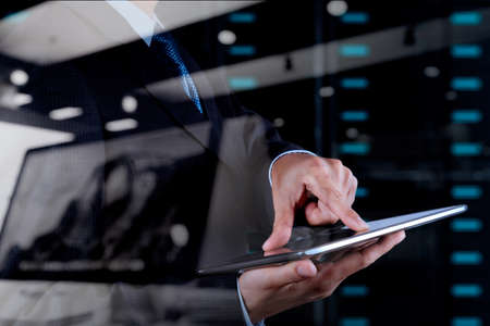 server technology: double exposure of businessman hand using tablet computer and server room background