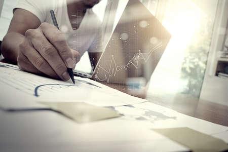 negócio: documentos de negócios na mesa de escritório com telefone esperto e tablet digital e gráfico de negócio com diagrama de rede social e homem que trabalham no fundo