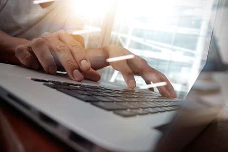 typing: Hombre de negocios de la mano, trabajando en equipo portátil en el escritorio de madera como concepto, joven hombre escribiendo estudiante en la computadora sentado en la mesa de madera