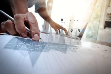 recursos financieros: documentos de negocios en la mesa de la oficina con el teléfono inteligente y el ordenador portátil y el negocio gráfico con el diagrama de la red social y el hombre que trabajan en segundo plano