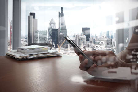 double exposure of businessman hand use smart phone with office workspace Banco de Imagens