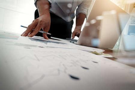 documents d'affaires sur la table de bureau avec téléphone intelligent et l'ordinateur portable et le graphique des affaires avec diagramme de réseau social et de l'homme qui travaillent en arrière-plan