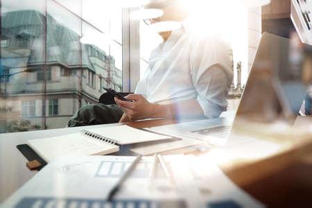 zakelijke documenten op kantoor tafel met slimme telefoon en digitale tablet en grafiek business diagram en man aan het werk op de achtergrond Stockfoto