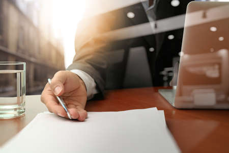 contracts: double exposure of businessman or salesman handing over a contract on wooden desk Stock Photo